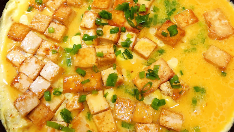 豆腐炒鸡蛋,撒入葱花,待鸡蛋凝固翻炒鸡蛋。