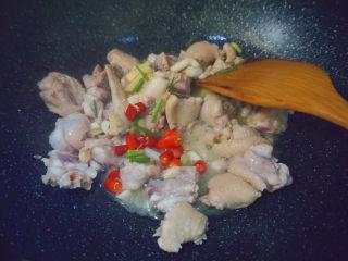 三黄鸡炖土豆,倒入蒜姜红辣椒配料翻炒3分钟