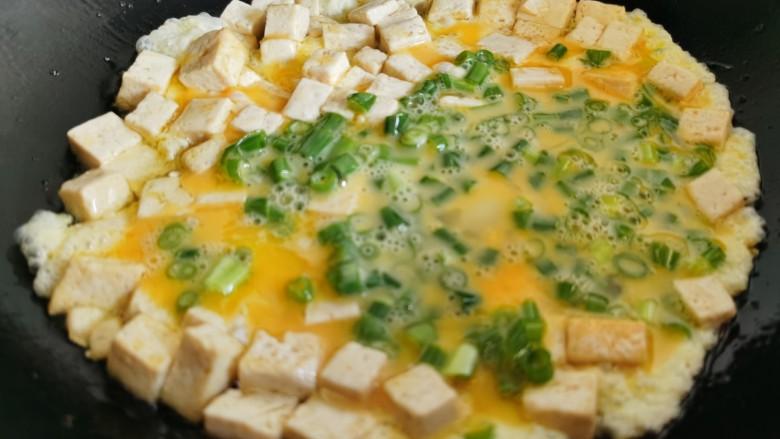 豆腐炒鸡蛋,然后倒入蛋液,快速翻炒。