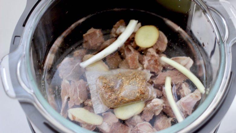 牛腩炖萝卜,放入炖牛肉调料包,剩下的葱和姜片,倒入不超过水位线的清水。
