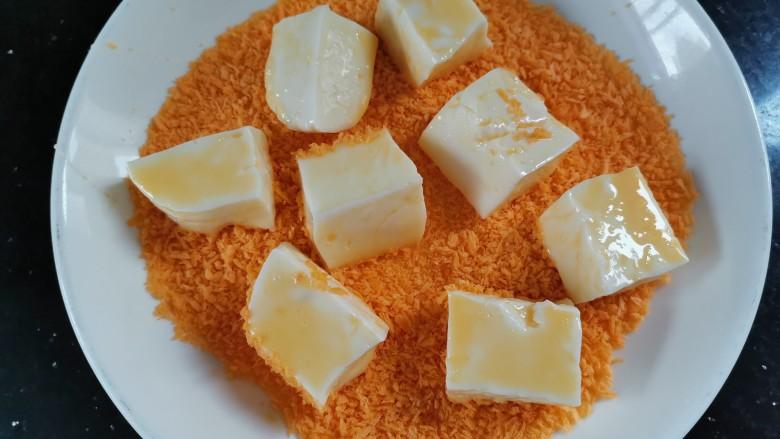 炸奶冻,裹好蛋糊的奶冻放入面包糠里
