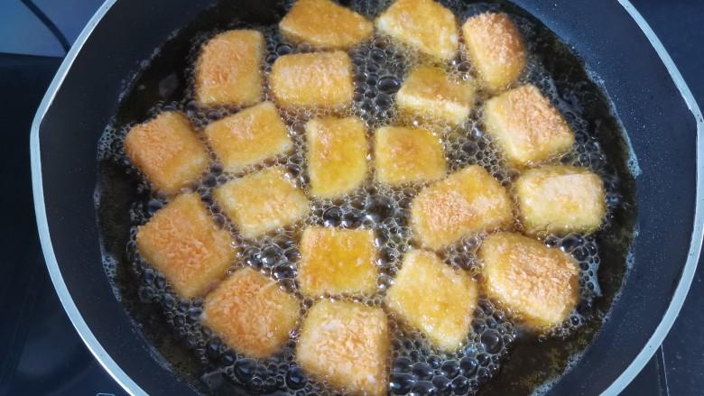 炸奶冻,锅里倒入适量的油,油温六成热放入奶冻炸,一面金黄翻另一面炸,全程用中火炸(不能炸太久,不然里面会化掉)