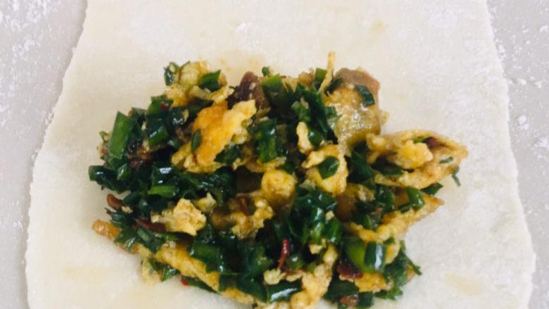 韭菜锅贴,用勺子把韭菜鸡蛋馅放入面皮上,沿着一个方向卷好即可~