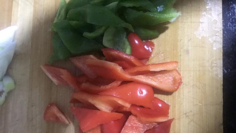 家常烧豆腐,把青椒和红椒先从中间切开成两片,再切成粗条,然后再切成三角形的块状