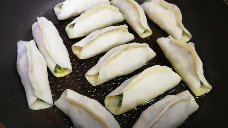韭菜锅贴,平底锅倒入适量油,油温5成热放入生胚,中小火煎一分钟。