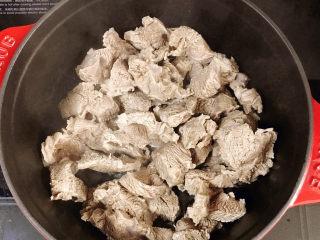 牛腱子炖萝卜,铸铁锅中放油,放入牛腱子肉