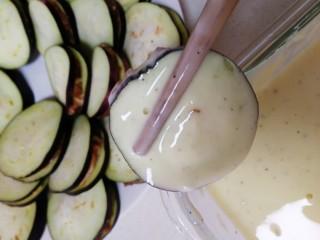 炸茄盒,锅里倒入适量油,中小火油温3成热,把茄盒放入面糊里裹匀。