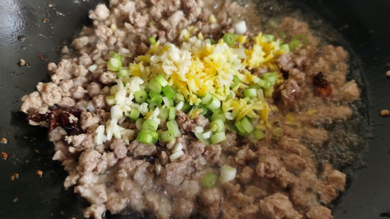老北京炸酱面,肉煸炒至变色,加入姜、蒜和一半的葱花翻炒。葱花不要都加进去,留下一半备用。