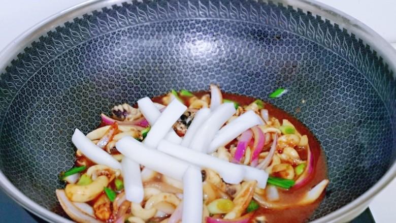 葱爆鱿鱼,按个人口味加入盐,再放入焯水的年糕,大火烧开煮1分钟。