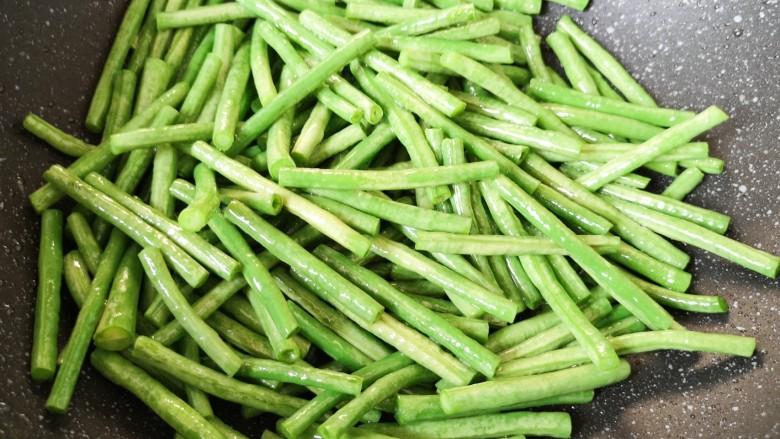 干煸豇豆,大火翻炒至豇豆变色。