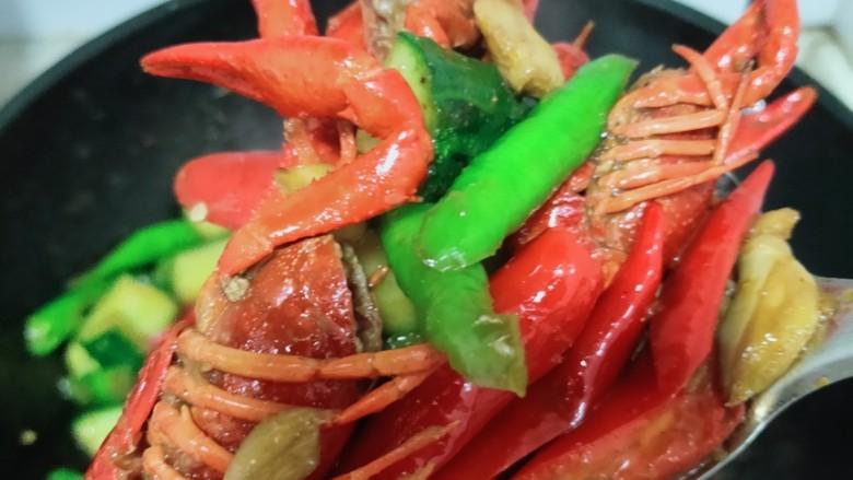 爆炒小龙虾,还剩一点点水时,加入盘中的黄瓜和双椒,炒一分钟左右