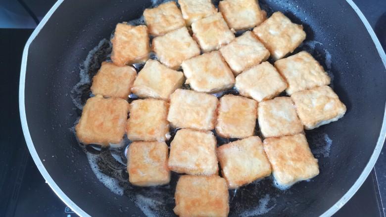 家常烧豆腐,锅里倒入适量的油,油热放入豆腐煎至两面金黄