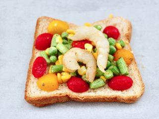 虾仁芝士吐司汉堡,把吐司片放在油纸上,依次均匀铺满混合好的食材和虾仁。