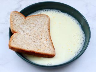 虾仁芝士吐司汉堡,先把一片吐司片浸泡在牛奶里。