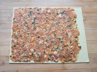 千张包肉,放上肉馅用勺子抹平,一个边留出来2厘米左右不要放肉馅,如图。