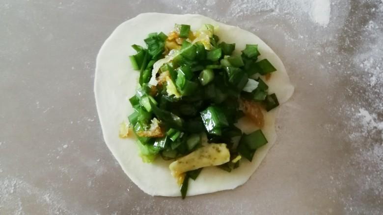 韭菜锅贴,取一份 用擀面杖擀成圆形 放入适量的馅料