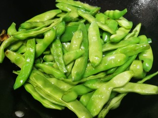 油豆角烧土豆,放入油豆角,中小火翻炒均匀,让每一根豆角都包上油,把豆角炒得更绿。