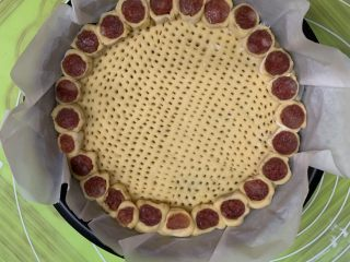 花边腊肠披萨,饼底插无数小孔。