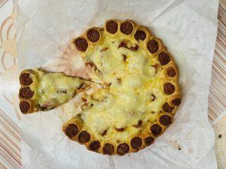 花边腊肠披萨,用剪刀剪一块。