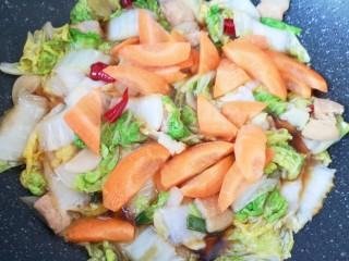 白菜炖豆腐,下入胡萝卜片翻炒均匀。