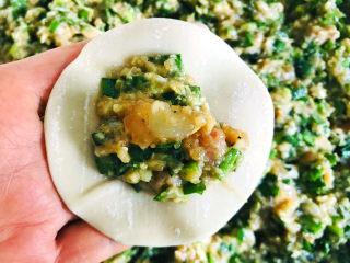 白菜虾仁韭菜猪肉饺子,取适量的饺子馅,放在饺子皮的中间,包成饺子