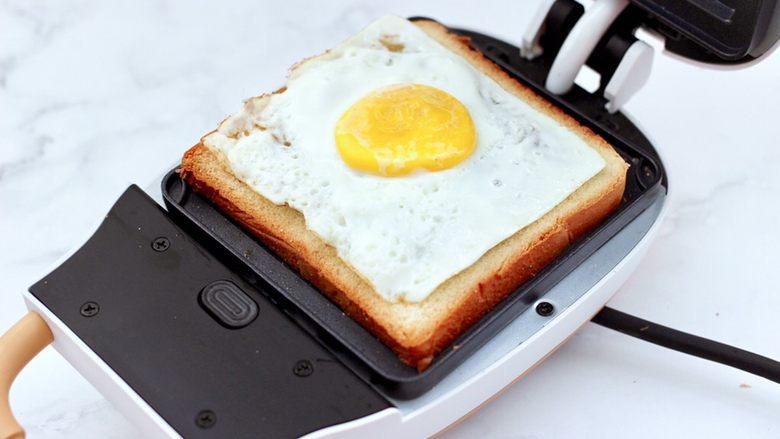鸡蛋蜜豆热压三明治,再把煎好的鸡蛋码放在上面。