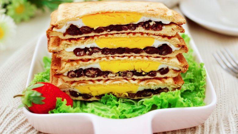 鸡蛋蜜豆热压三明治,做好的三明治,用刀一切两半就可以享用了。