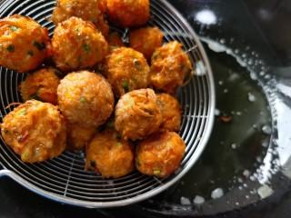 炸胡萝卜丸子,炸至丸子金黄时捞出装盘。