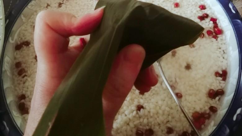 红豆粽子,用粽叶向下盖住漏斗顶部交汇处 用手捏出一个角。
