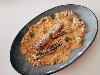 豆根糖,留下的20克熟黄豆面 放入盘中 将烤好的豆根糖 裹上黄豆面。