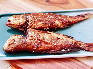 风味烧烤鱼,香酥可口的风味烧烤鱼出锅咯,香味飘满了整个房间,放入盘中撒上适量白芝麻即可享用了。