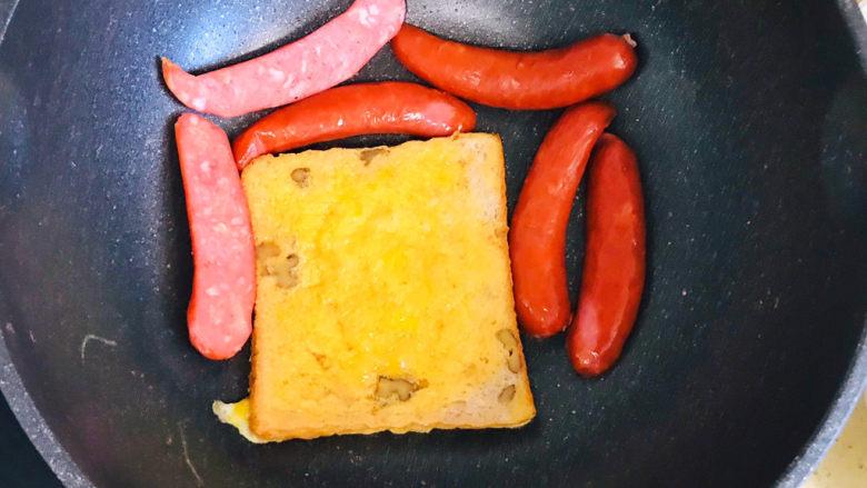 一个人的趣味早餐—笑脸吐司,吐司煎好后,将香肠码放进锅里,不需要再加油,继续小火将香肠煎热
