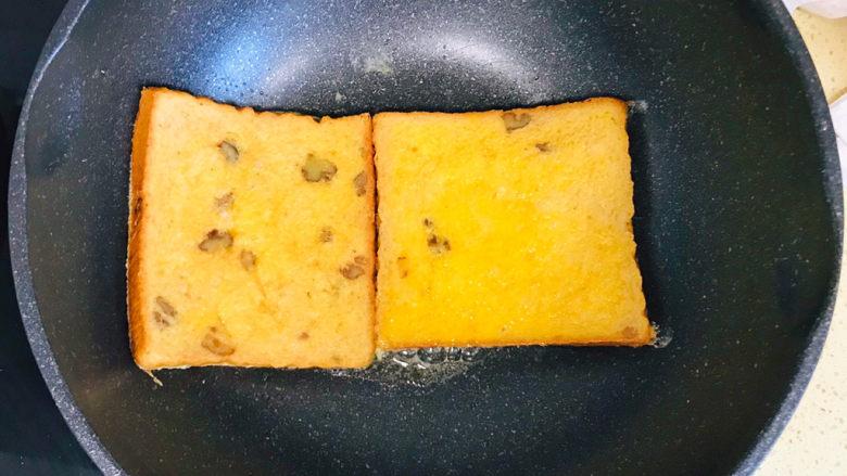 一个人的趣味早餐—笑脸吐司,不粘锅烧热,倒入少许<a style='color:red;display:inline-block;' href='/shicai/ 851'>橄榄油</a>,将吐司片码放进锅里,转小火,慢火煎制