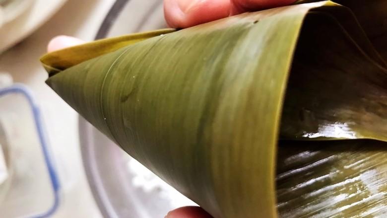 红豆粽子,粽叶煮软后,将粽叶折成三角