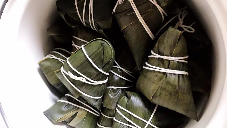红豆粽子,然后将粽叶顺着三角折包起来,再用绳子绑好