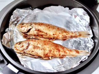风味烧烤鱼,炸篮上铺上锡纸,放入腌制好的鱼。