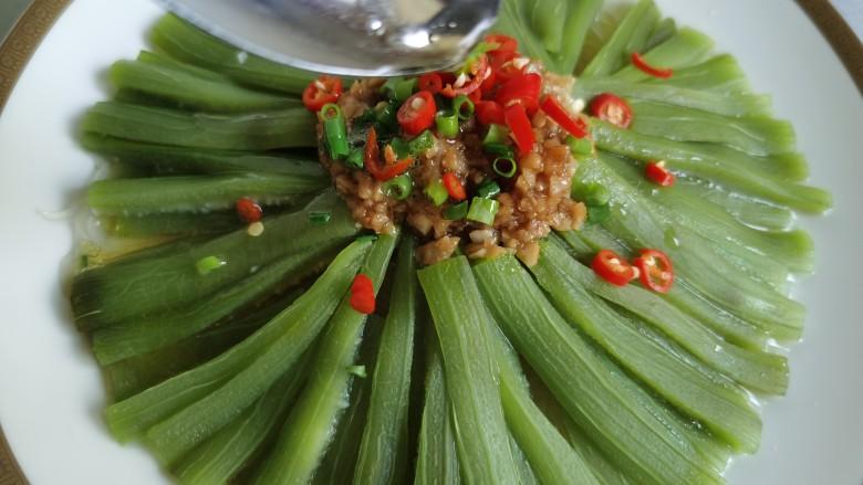 蒜蓉蒸丝瓜,将辣椒和香葱放到蒸熟的丝瓜上面。用炒锅将油烧热,将热油浇到辣椒上。