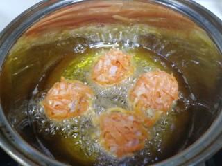 炸胡萝卜丸子,中小火油温3成热,放入胡萝卜丸子。(团成丸子)
