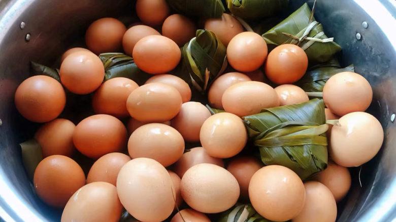 红豆粽子,蒸锅底摆上粽叶防止粘锅依次摆上粽子再摆上一层鸡蛋最好是一个挨一个夹紧的摆放这样蒸出来粽子更紧实