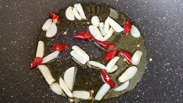 清炒莴笋丝,炒锅内倒适量的食用油烧热,下入蒜片和干红辣椒炒香。