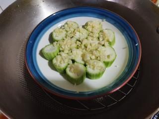 蒜蓉蒸丝瓜,锅里放上蒸架,倒入清水。把盘子放在蒸架上,蒸5到8分钟。