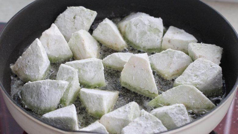糖醋茄子盖饭,锅中倒入比平时炒菜多一些的食用油,将裹满淀粉的茄子放入锅中开小火煎制。
