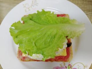 鸡蛋芝士全麦三明治,铺上一片生菜。