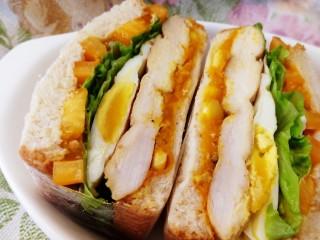 甜玉米雞胸肉全麥三明治,保鮮膜包緊,對半切開。雞胸肉低脂,蛋白質含量高,易被吸收。