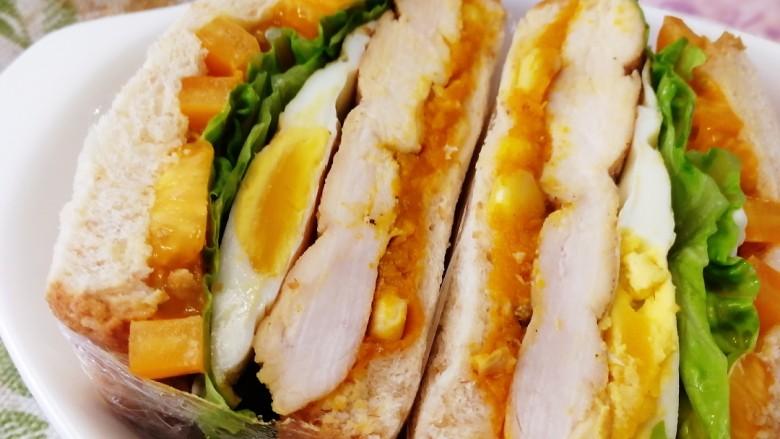 甜玉米鸡胸肉全麦三明治,保鲜膜包紧,对半切开。鸡胸肉低脂,蛋白质含量高,易被吸收。