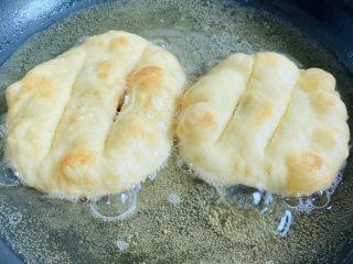 炸油饼,炸至鼓起再翻面炸至两面金黄即可