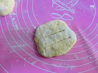 炸油饼,用手将面团摁扁再划两刀