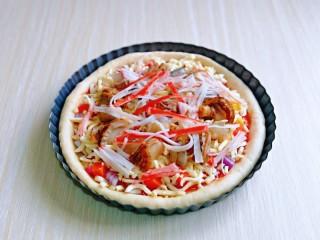 培根火腿披萨,再摆放上腌制好的海鲜,培根,蟹肉丝。