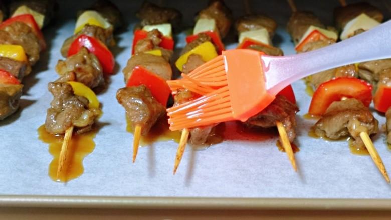 孜然羊肉串,15分钟后取出烤盘,将肉串两面刷上食用油。