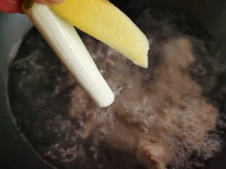 孜然排骨,加入姜片和葱段。